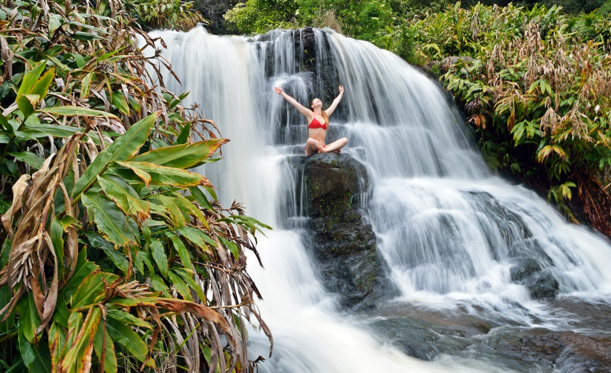 Sitting in the middle of a waterfall on Kaua'i.